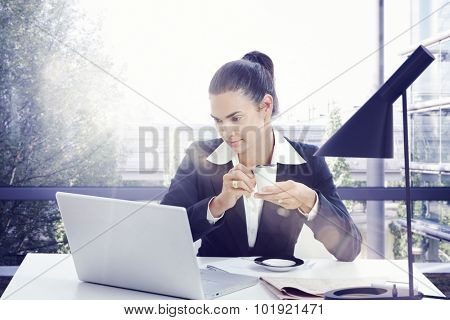 Businesswoman working with laptop in sunny office drinking morning coffee.