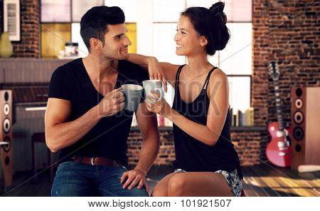 Romantic young couple sitting at home, drinking tea, smiling.