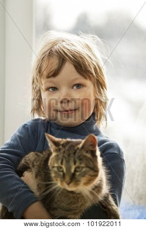 Happy kid with dirty face with cat in her arms in home