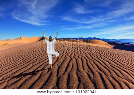 Yoga in the desert. Orange sand dunes in Death Valley, California. A middle-aged woman in a white performs asana