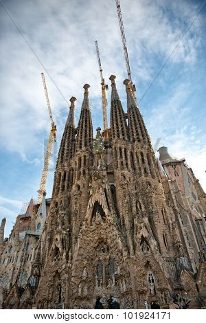 Exterior view of the ornate spires of the Familia Sagrada, Barcelona, Spain with industrial cranes, a historic landmark Roman Catholic Church still under construction, view looking up