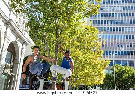 Happy friends doing parkour in the city on a sunny day