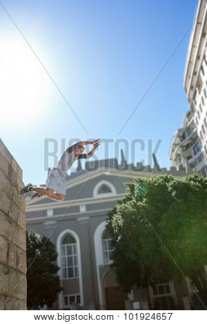 Man doing parkour in the city on a sunny day