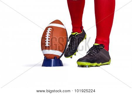 American football player about to kick the ball on white background