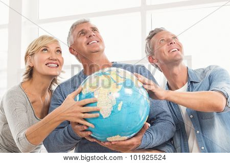 Happy business colleagues holding terrestrial globe and looking above