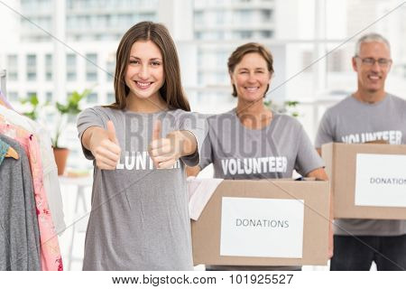 Portrait of smiling volunteers holding donation boxes in the office
