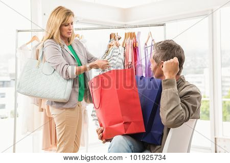 Man sitting and waiting for his shopping woman in clothing store