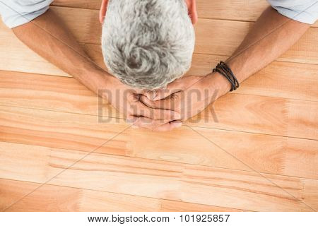 Overworked casual businessman leaning on wooden desk in the office