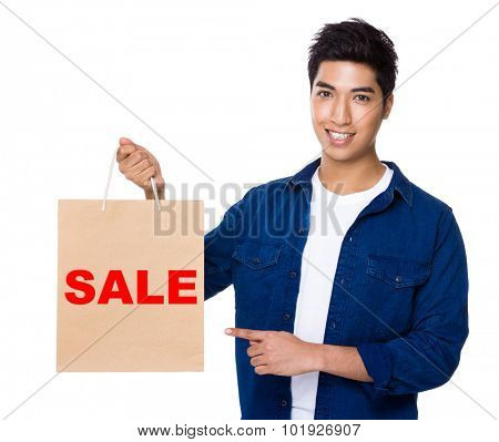 Man finger point to shopping bag for showing a word sale