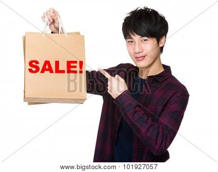 Happy young shopper with finger point to paper bag for showing a word sale!