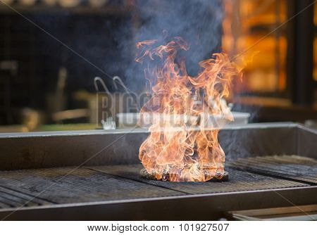 Meatballs in flames on a grill