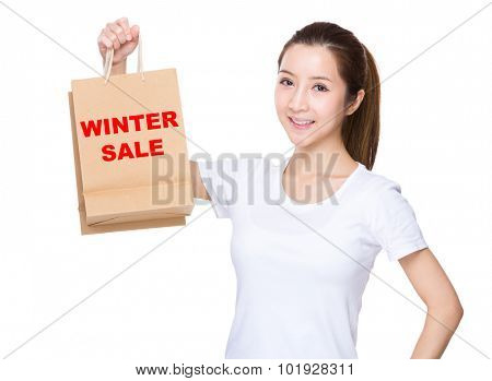 Woman hold with shopping bag and showing phrase of winter sale