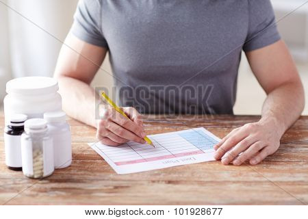 sport, fitness, healthy lifestyle and people concept - close up of man with protein jars writing diet plan at home