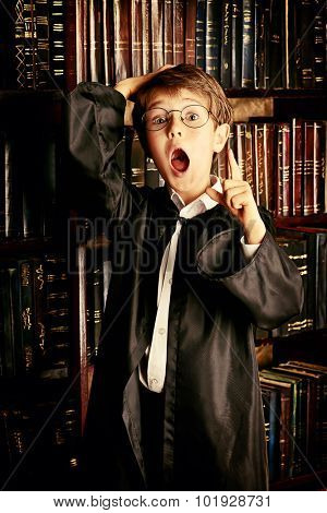 Cute boy stands in the library by the bookshelves with many old books, he is surprised. Educational concept. Science. Vintage style.