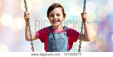 summer, childhood, leisure, friendship and people concept - happy little girl swinging on swing over blue lights background