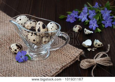 Quail Eggs In A Glass Gravy Boat And Periwinkle Flowers On An Old Wooden Background. Easter concept