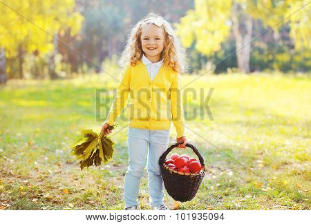 Little Smiling Girl Child With Maple Leafs And Basket With Apple In Autumn Day