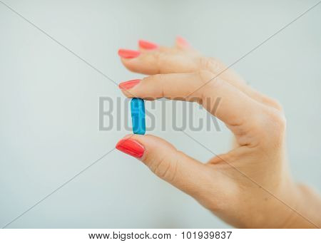 Women's fingers with pink manicure taking blue pills