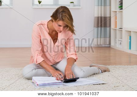 Woman Calculating Invoices With Calculator