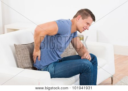 Man On Sofa Suffering From Backpain