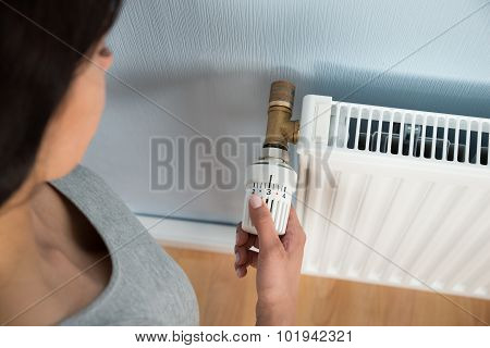 Young Woman Turning Thermostat On Radiator