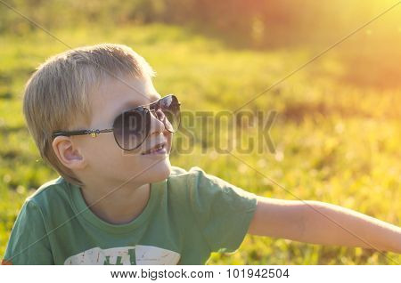 Cute Adorable Child In Sunglasses Sitting On Green Grass In The Park