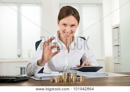 Businesswoman Calculating Invoice With Coins At Desk