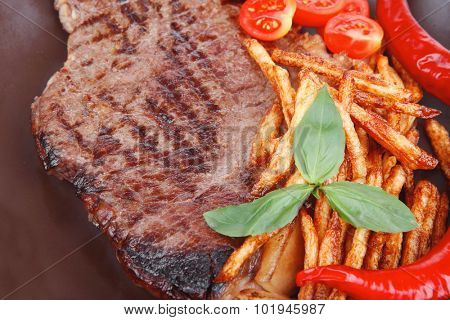 main course : grill beef steak with potato chips and fresh cherry tomato , red hot chili peppers on plate isolated on white background