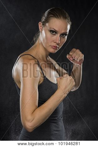 Strong Woman in Combat Pose Looking at Camera