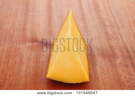 chunk of aged french gruyere or cheddar cheese in black shell on wooden table