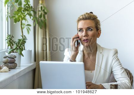 Business woman in the home office working on laptop and speaks on a cell phone.