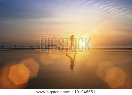 Silhouette of a young jogger girl running through the surf at amazing sunset.