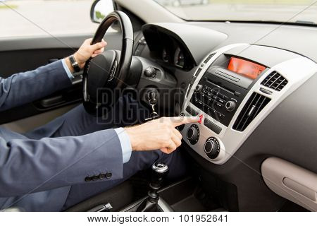 transport, business trip, breakdown, technology and people concept - close up of young man in suit driving car and switching emergency signal button
