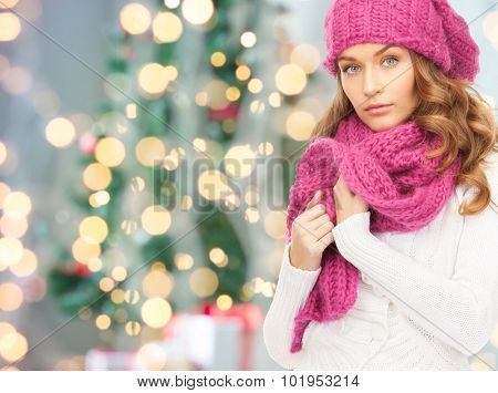 winter holidays, christmas and people concept - young woman in hat and scarf over christmas tree lights background