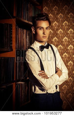 Handsome well-dressed young man stands by bookshelves in a room with classic interior. Fashion shot.