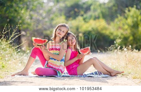 Two girls and a juicy red watermelon.