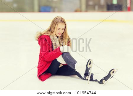 people, sport, trauma, pain and leisure concept - young woman fell down on skating rink and holding to her knee