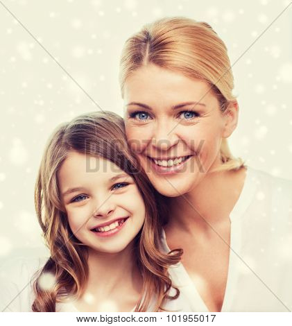 family, childhood, motherhood, people and happiness concept - smiling mother and little girl over snowflakes background