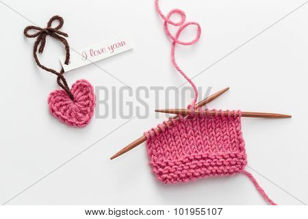 Crochet heart with Love Yarn tag and incomplete knitting project