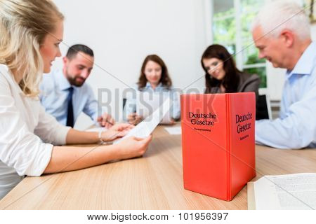 Lawyers in meeting negotiating agreement and reading documents