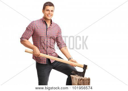 Young guy in a checkered shirt holding an axe and posing behind a log isolated on white background