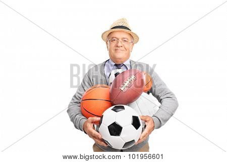 Joyful mature man holding bunch of different kind of sports balls and looking at the camera isolated on white background