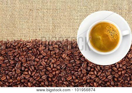 Close-up Of Roasted Coffee Beans And Coffee Cup Over Linen Texture