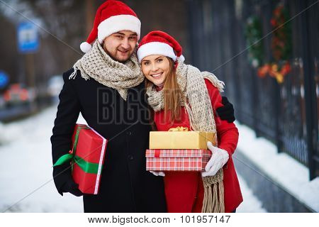 Amorous couple in Santa caps holding giftboxes