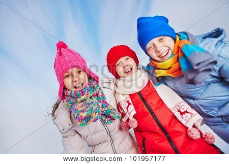 Happy children in winterwear looking at camera with smiles