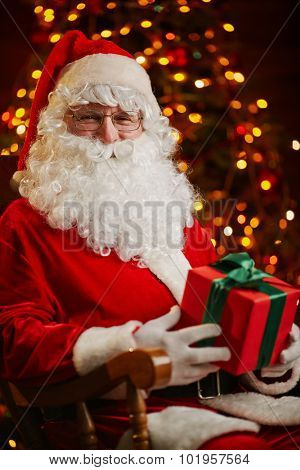 Happy Santa Claus with package looking at camera on background of sparkling firtree