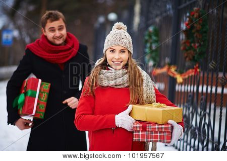 Cute girl with giftboxes looking at camera on background of young man