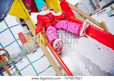 Two girls in winterwear spending leisure outdoors