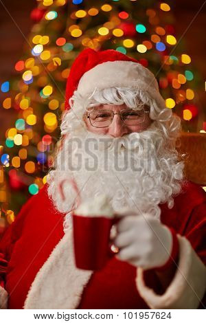 Santa Claus with cup of latte looking at camera