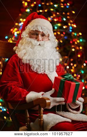 Happy Santa with box looking at camera while sitting by sparkling firtree